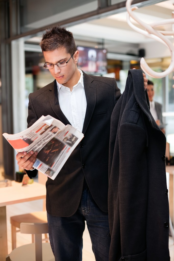 business young man  concerted  reading the newspaper while attaching his coat, interesting news